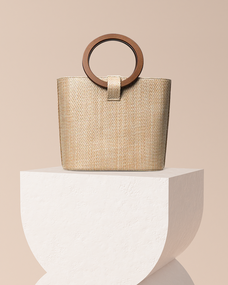 Constance natural rattan bag front view on pedestal with wood handle