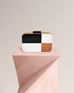 Julie black and white wood clutch front view on pedestal