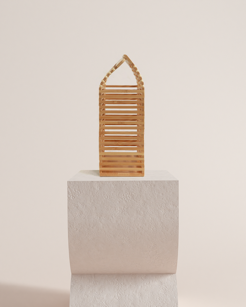 Lara natural bamboo basket bag side view on a pedestal