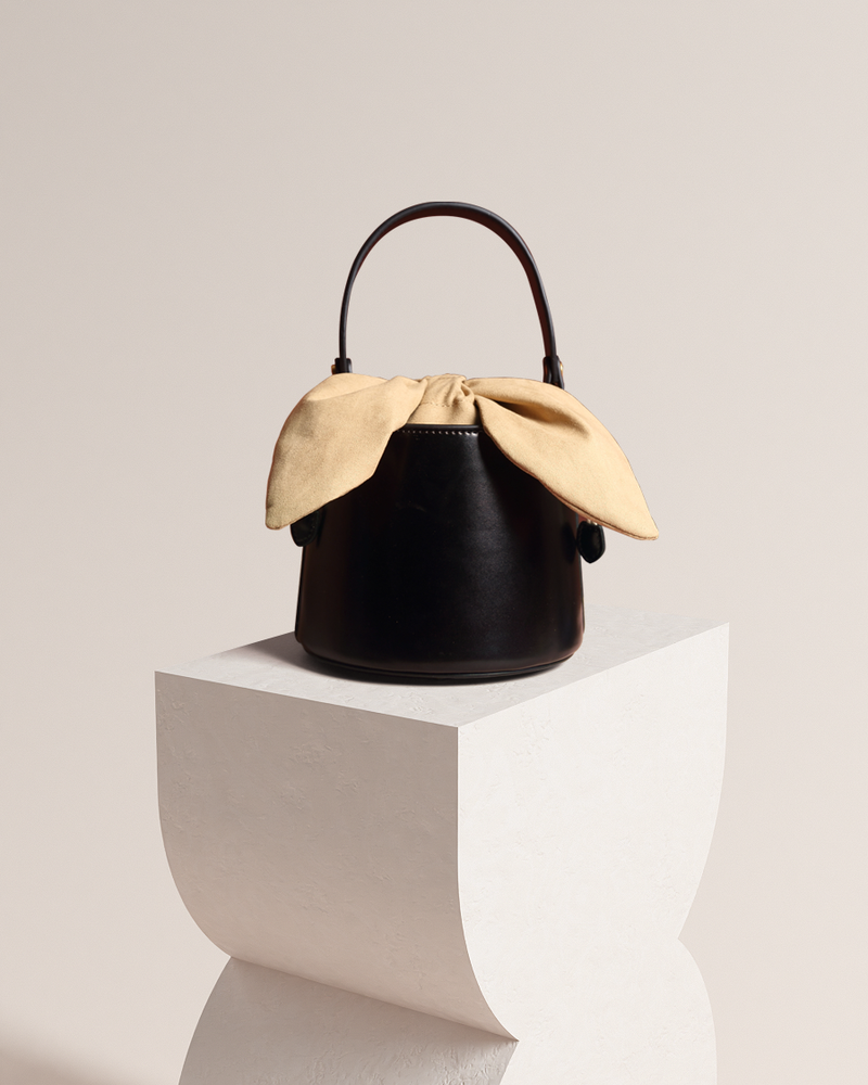 Esme black bucket bag front view on pedestal
