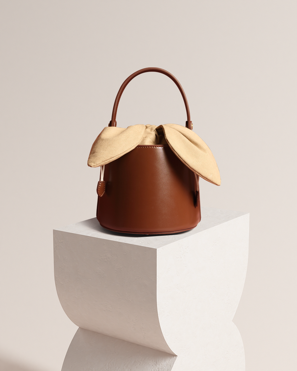 Esme brown bucket bag front view on pedestal