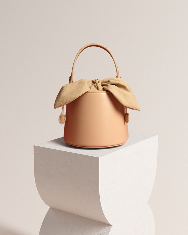 Esme beige bucket bag front view on pedestal