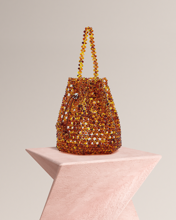 Laurie acrylic beads bucket bag side view on pedestal
