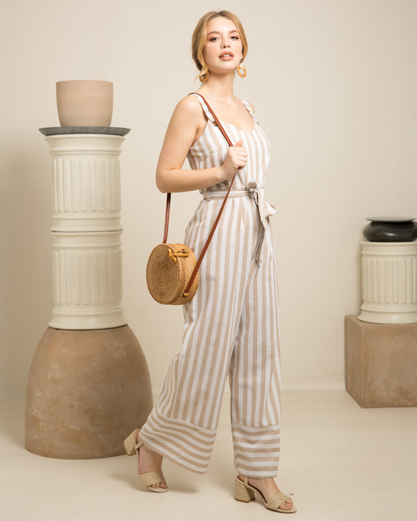 Blonde woman wearing stripped dress holding Bali natural rattan and straw bag on set