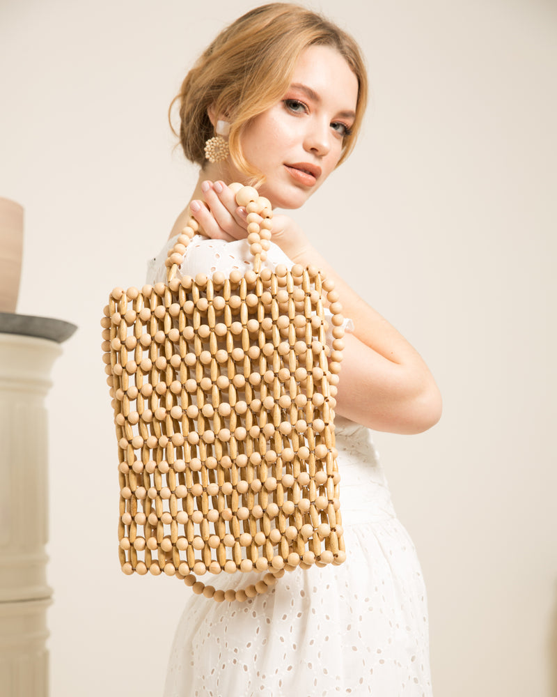 Blonde woman holding Cassey natural bamboo tote bag looking over shoulder