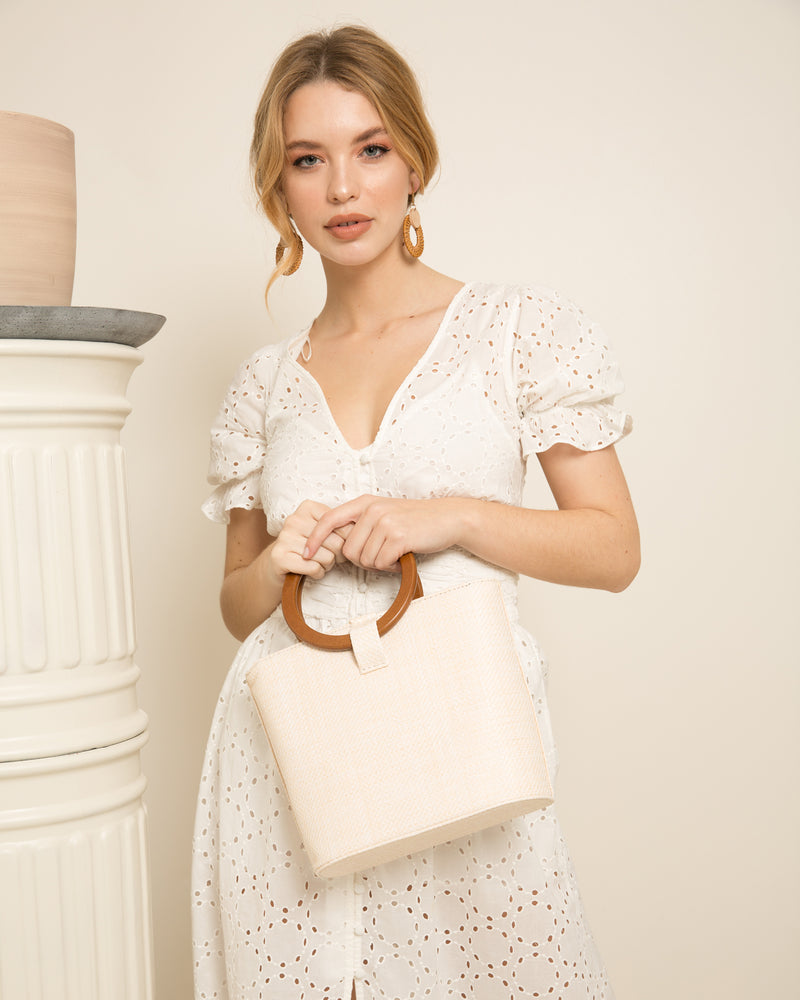 Blonde woman in white dress holding Constance rattan bag pale