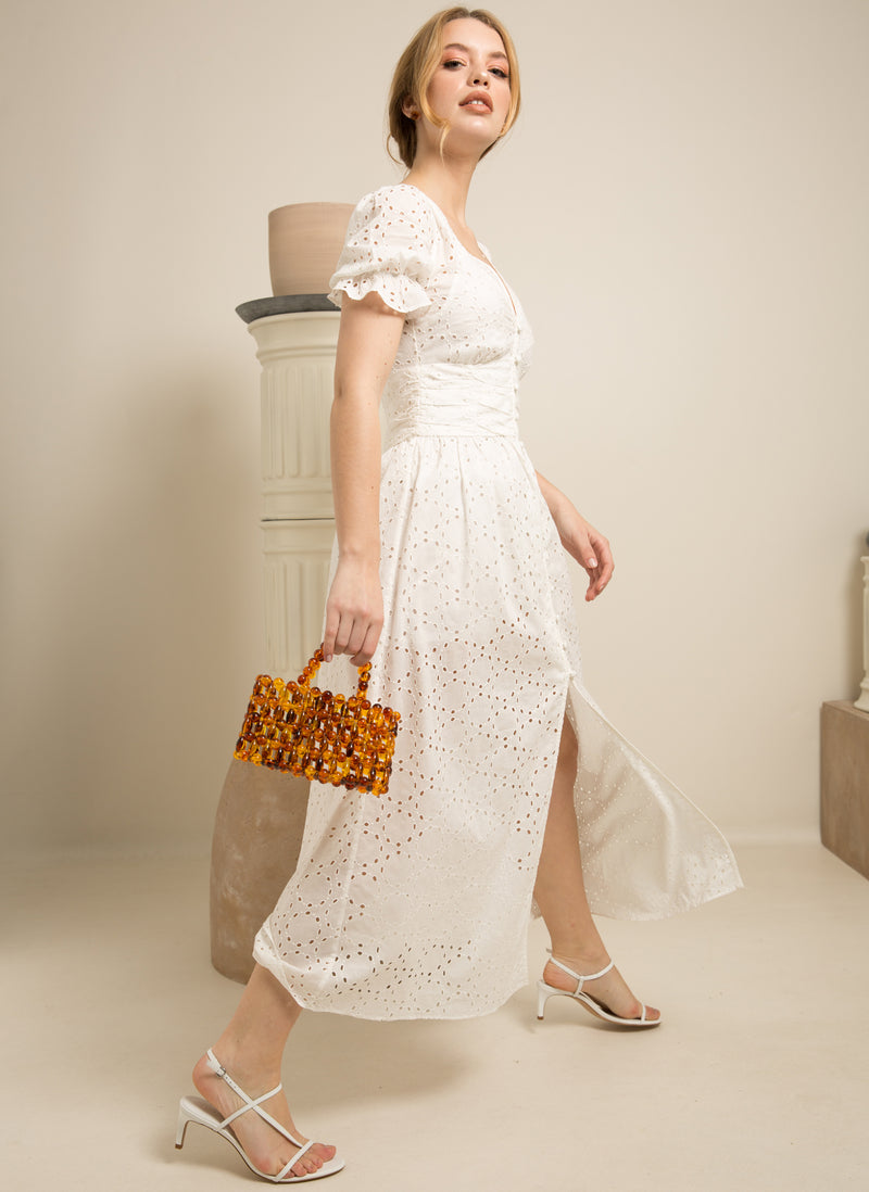 Blonde woman in white dress holding Vera tortoise acrylic beads clutch