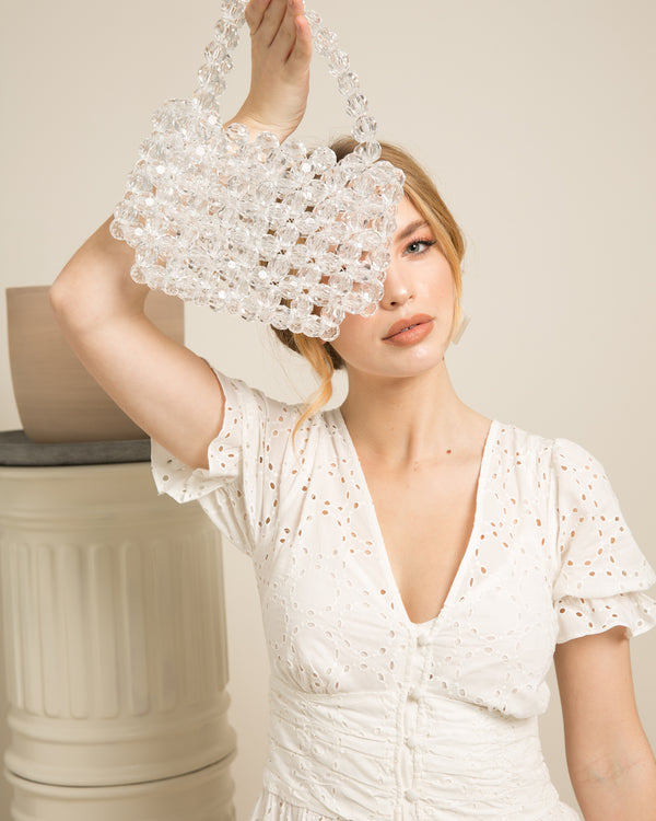 blonde woman with white dress holding Ivy clear acrylic beads clutch