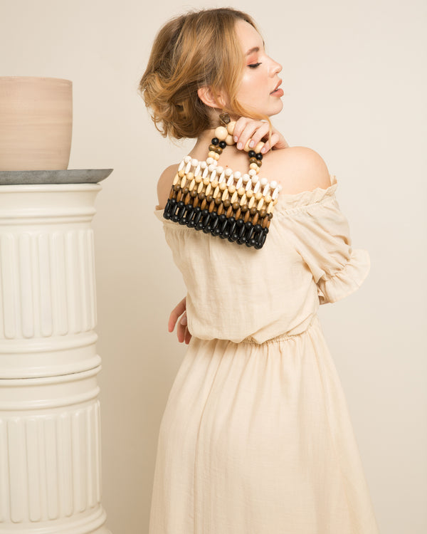 blonde woman holding tess multicolored bamboo beads clutch over shoulder on set