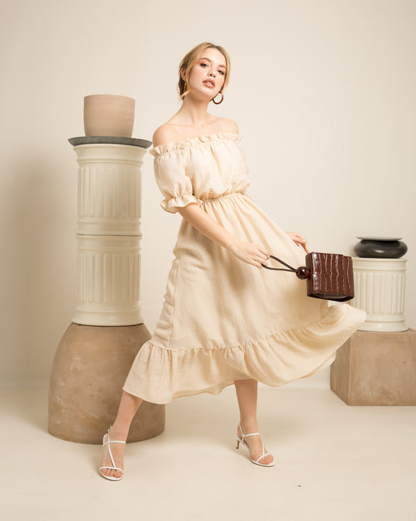 blonde wearing white dress holding brown kaya leather bead bag on set