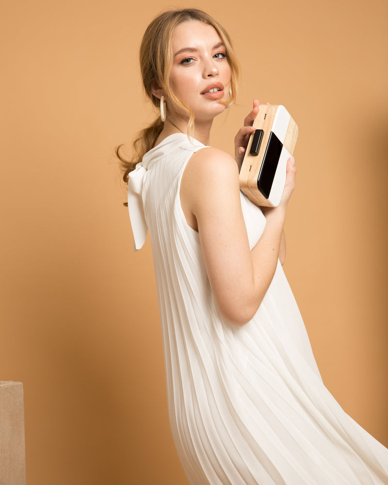 blonde woman in white dress holding Julie black and white wood clutch