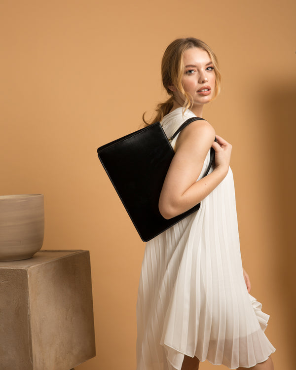 blonde woman in white dress wearing black Diana leather tote bag on shoulder