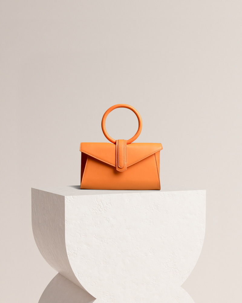 Simone leather bag in orange front view on pedestal