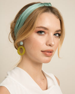 blonde woman wearing Faye turquoise turband and light green earrings on set