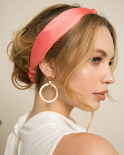 blonde woman wearing Faye magenta turband with ivory earrings on set