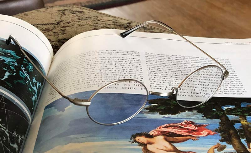Oval Silver Metal Diopter Strength Readers on a book