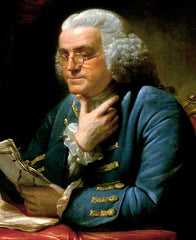 Benjamin Franklin wearing glasses and reading