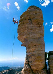 Rock climber near peak of tall rock formation