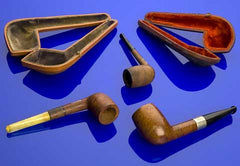 Still life of smoking pipes and pipe cases on blue background