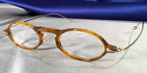 Side view of Capistranos tortoise shell and gold oval eyeglasses