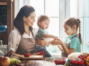 mother and two young kids making food in the kitchen