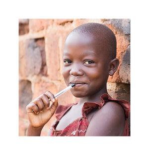 young african girl standing against brick wall with pen in her mouth smiling