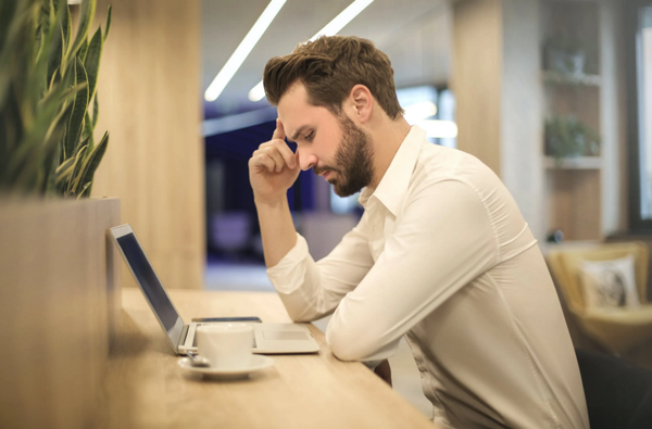 Man looking frustrated in front of his computer at the workplace