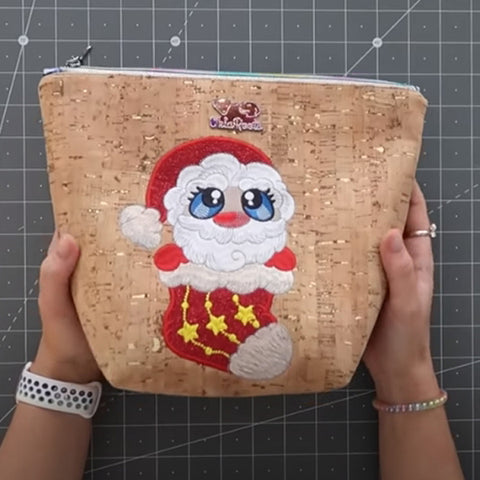 Picture of waterproof zip bag with Santa Buddy machine applique design on front.