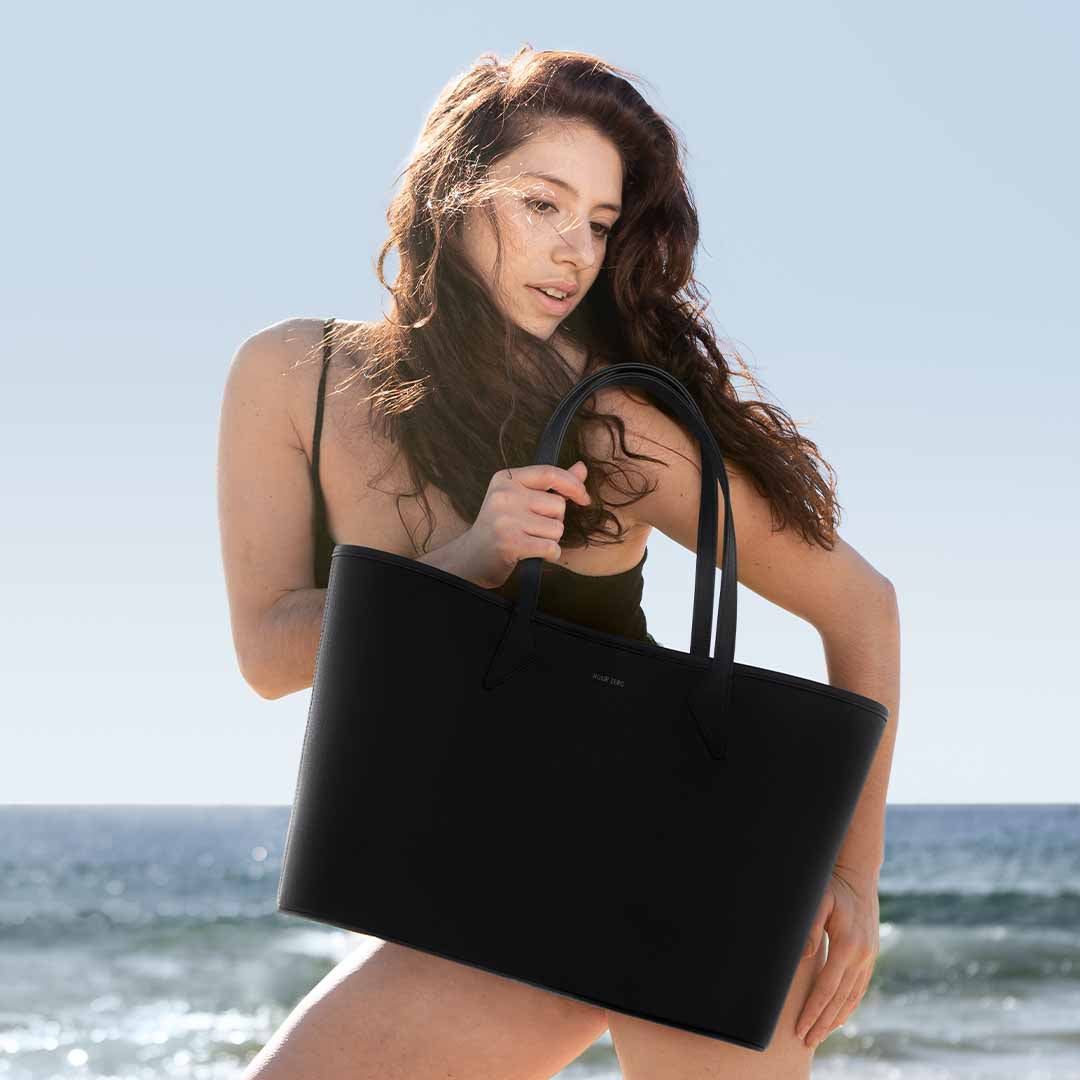 Chloe holding The Everything Tote at the beach
