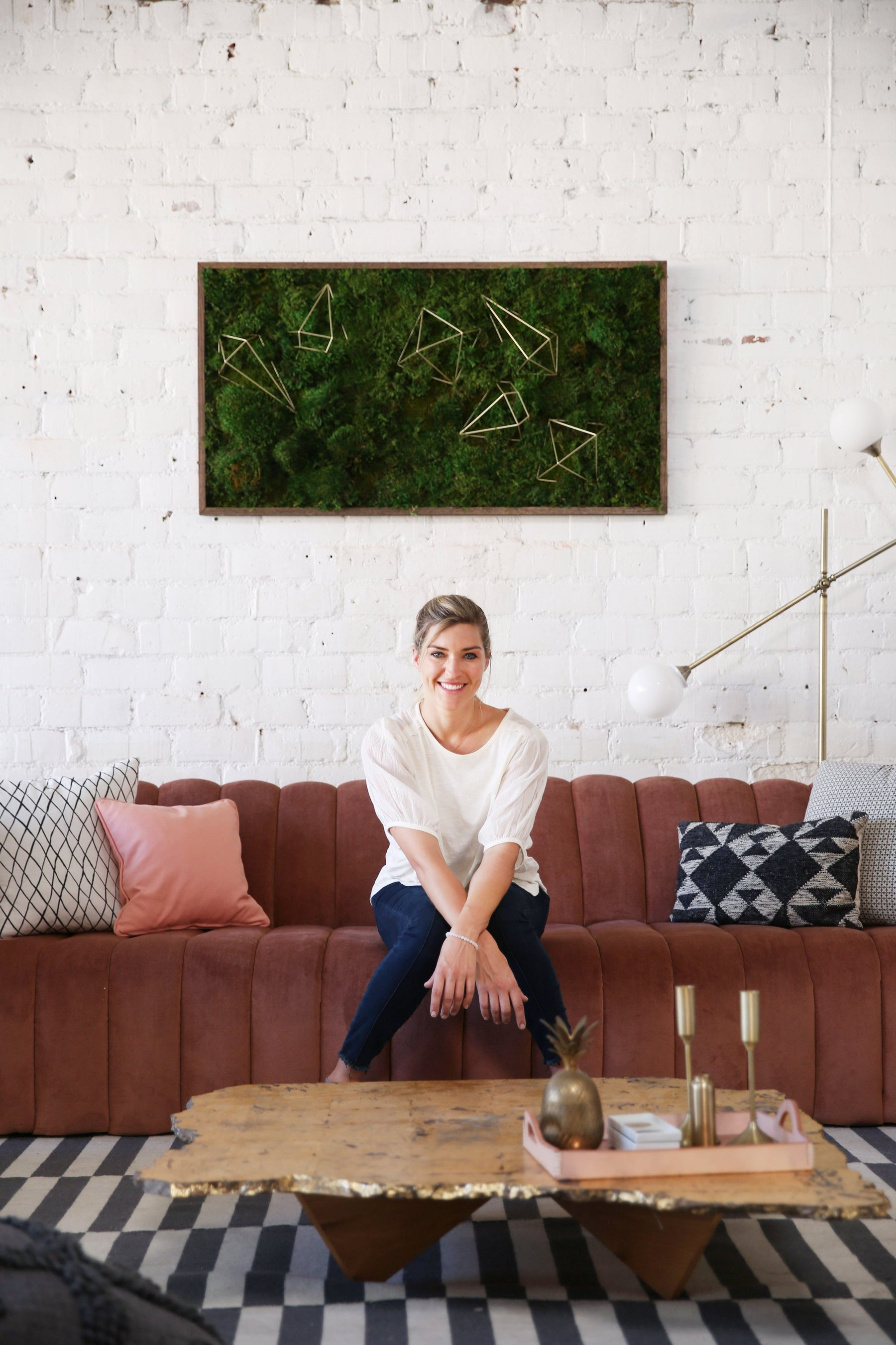 Kelley sitting on a couch with moss art behind her