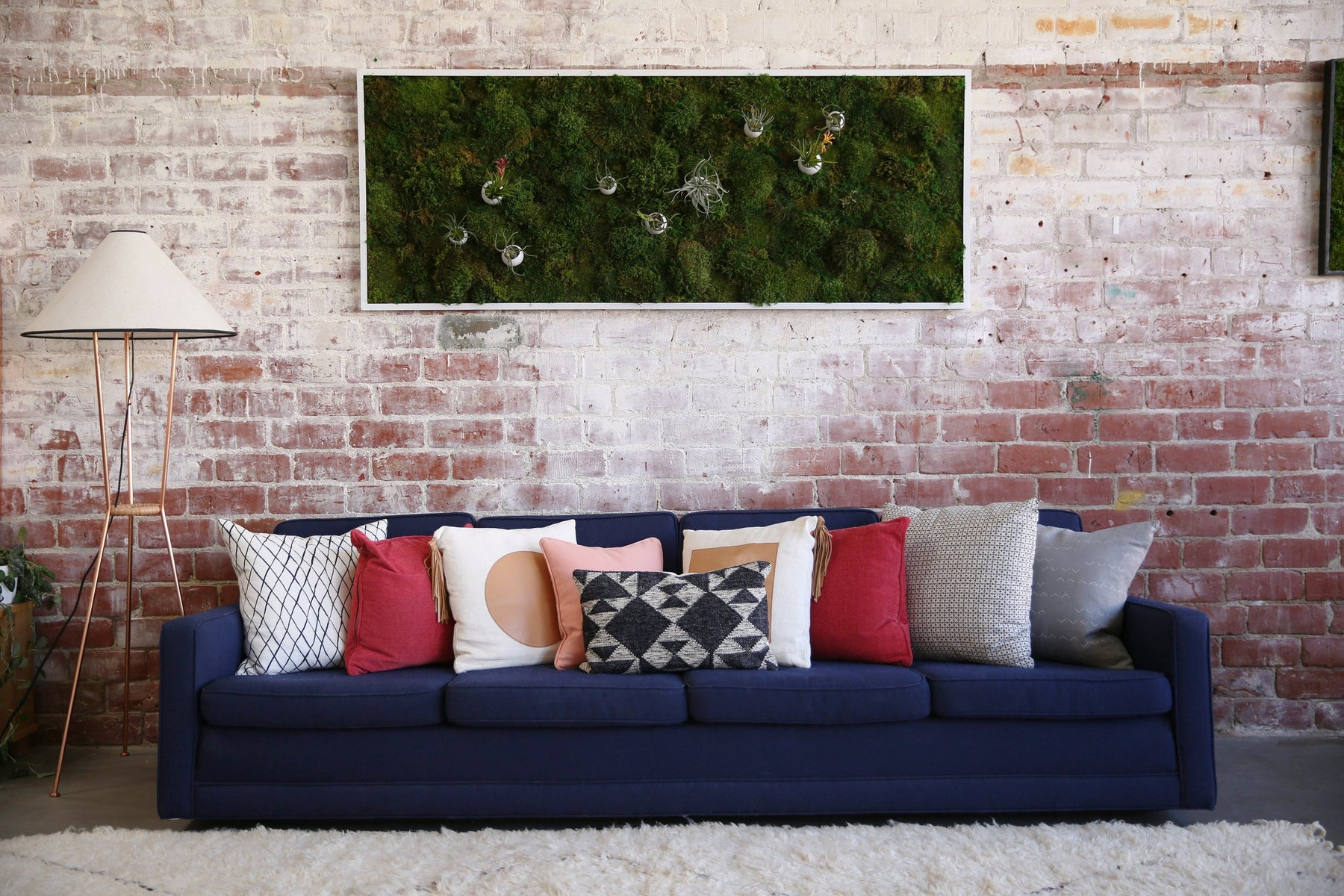 One of kelley's natural moss art pieces hanging on a distressed brick wall above a blue couch covered in many pillows
