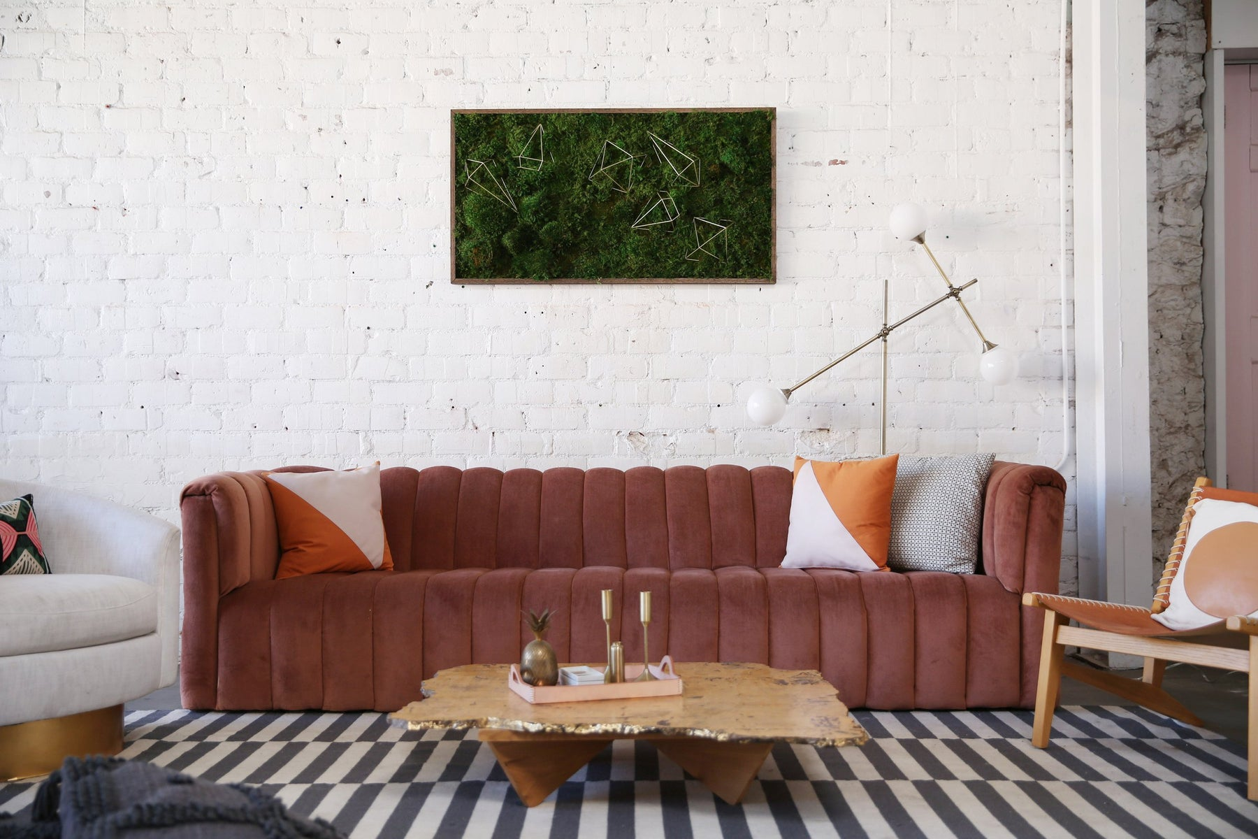 Another of kelley's pieces hung above a pink couch on a white brick wall