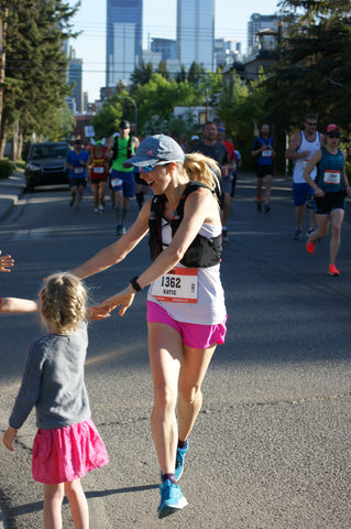 woman marathoner high fiving her kids