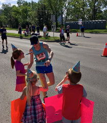 marathon racing woman with kids cheering