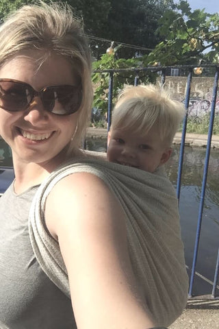 Blonde woman in a grey top and sunglasses with a blonde baby on her back in a grey wrap on a sunny day