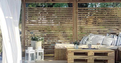 Wooden pergola with a pallet sofa and a white curtain