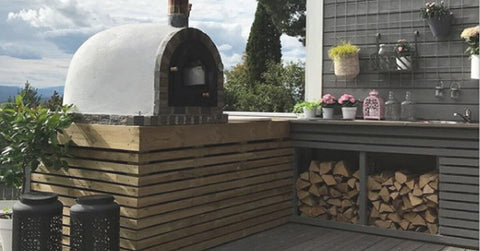 Outdoor kitchen with stone oven and plant wall