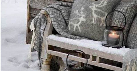 Cosy winter nook with snow, blankets and lanterns