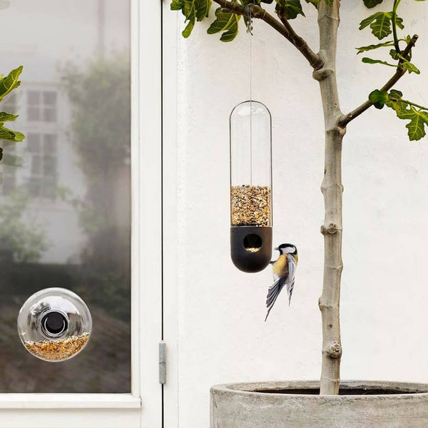 Eva Solo bird feeders with a bird feasting on the seed