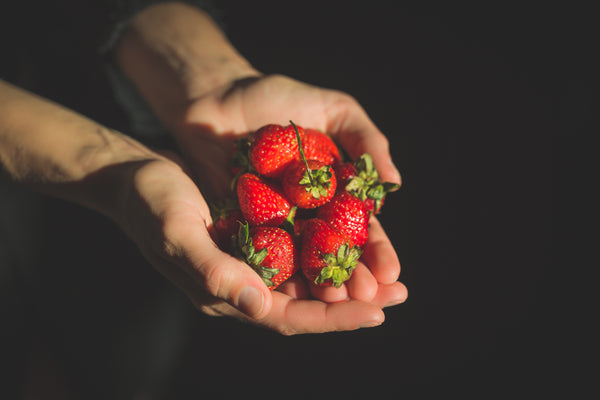 Hands offering strawberries.