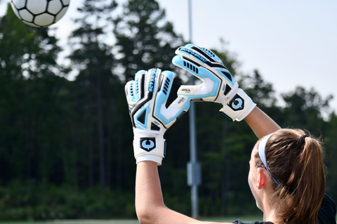 girl soccer goalie trying to catch the ball wearing Fury Sub-Z gloves