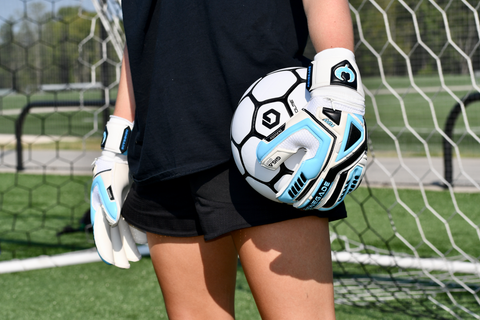 soccer goalie with ball on one hand