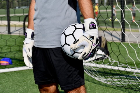 goalkeeper standing while holding the ball on the side with Fury UV gloves