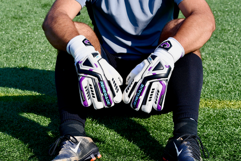 goalkeeper resting on the grass while wearing Renegade GK Fury UV gloves