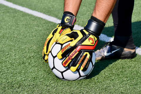 soccer goalkeeper wearing talon revolt gloves catching ball on the ground
