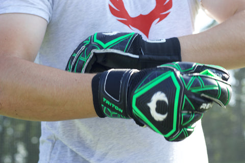 soccer goalkeeper adjusting the straps of triton raider gloves