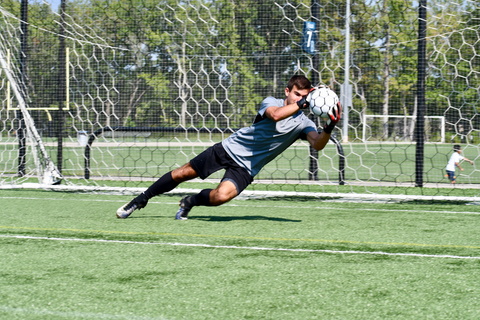 goalkeeper wearing vulcan raze gloves jumping towards the incoming ball to catch it