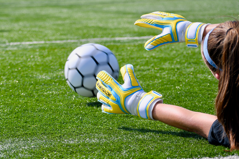 goalkeeper wearing vulcan shockwave gloves diving to the ground to catch the ball