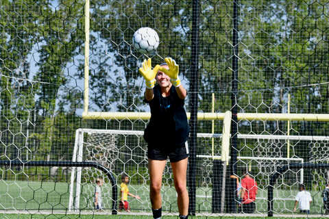 girl soccer goalie with vulcan surge gloves trying to catch the ball from above