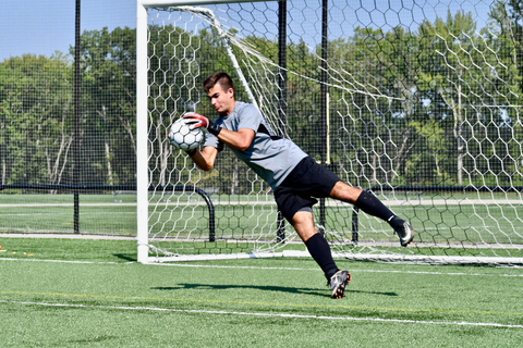 soccer goalie with vulcan torch gloves diving to catch the ball